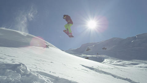 SLOW MOTION: Snowboarder jumping in fresh snow Footage