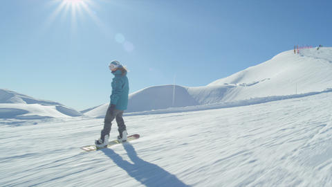 SLOW MOTION: Girl snowboarding on a sunny day Live Action