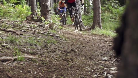 Downhill bikers riding through woods Footage