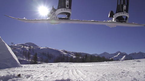 SLOW MOTION: Snowboard falling on groomed snow Live Action