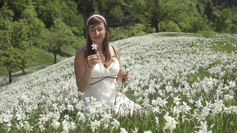 SLOW MOTION: Woman in white dress smelling flowers Footage