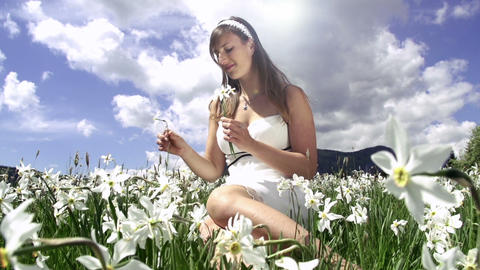 Woman in white dress gathering flowers Footage