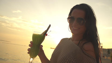 Beautiful young woman sipping cocktail at sunset Footage