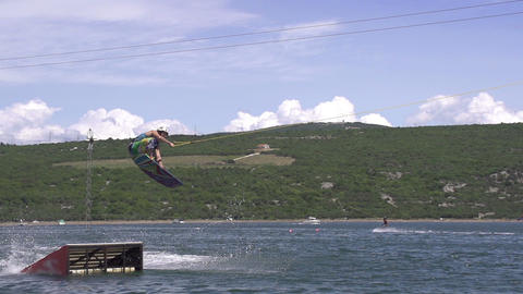 SLOW MOTION: wakeboarder jumps over the kicker Footage