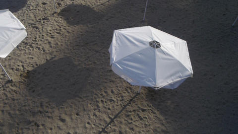AERIAL: White Umbrellas On The Beach stock footage