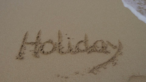 Word holiday written in the sand and washed away Footage