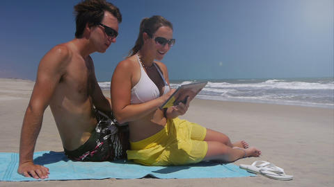 Young Couple Sitting On A Beach, Using Digital Tab stock footage