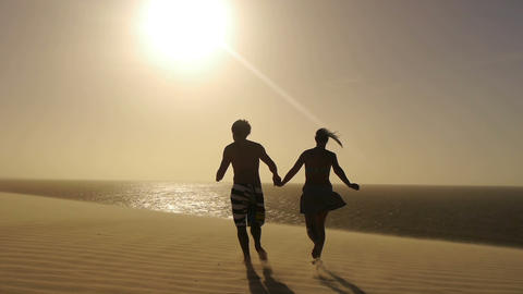 Young couple running towards the sun Footage