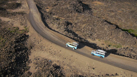 AERIAL: Surf cars driving along the rocky coast Footage