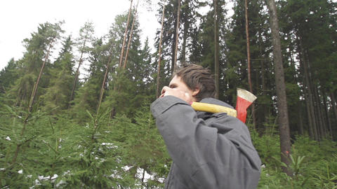 SLOW MOTION: Man with an axe walking in forest Footage