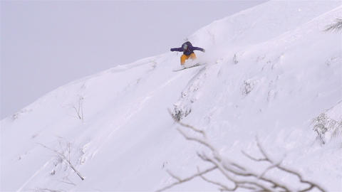 SLOW MOTION: snowboarder jumping over a cliff Footage