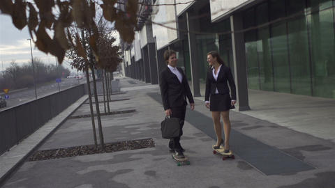 Cheerful business coworkers skateboarding to work Footage