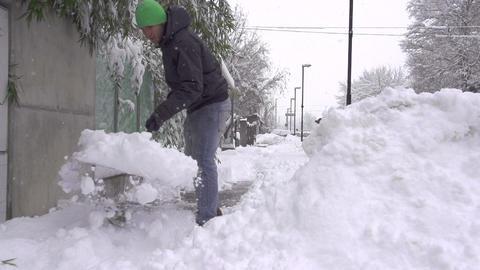 SLOW MOTION: Man shoveling snowy sidewalk Footage