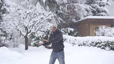 SLOW MOTION: Young man tossing a snowball Footage