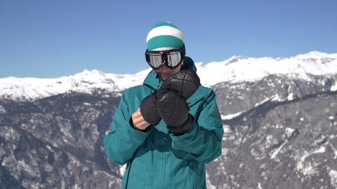 Snowboarder girl putting on gloves Live Action