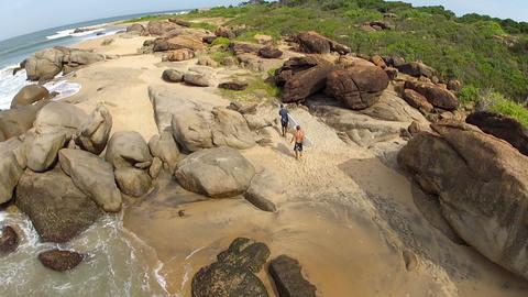 AERIAL: surfers walking on the coast Footage