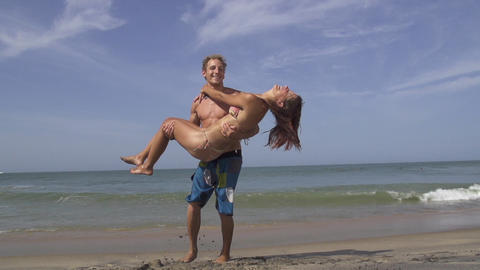 SLOW MOTION: Young man carrying his girlfriend on  Footage