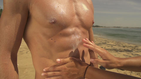 Woman applying sunblock on muscular man Footage