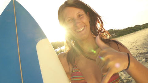 Smiling young woman showing surf sign with her han Footage