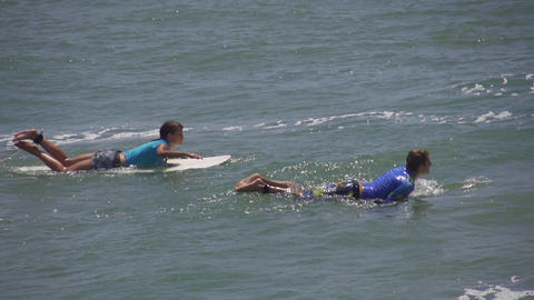 SLOW MOTION: Surfer boy and girl paddling Footage