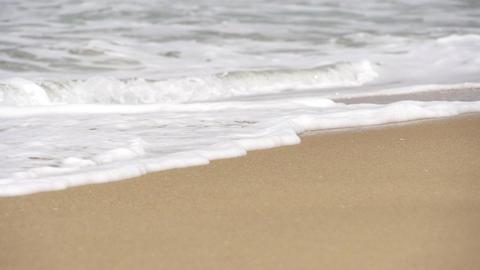 SLOW MOTION: Sea ??foam slides along the sandy bea Footage
