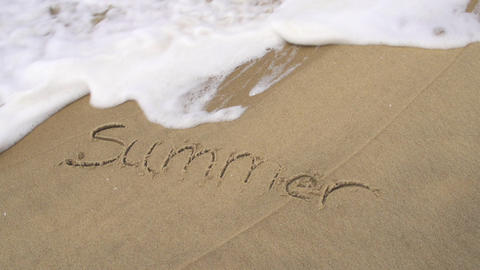 SLOW MOTION: Summer written in a sand and washed a Footage