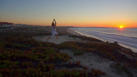 AERIAL: Woman doing yoga on top of the ocean cliff Footage