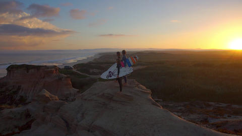 AERIAL: Surfers standing on top of cliffs at sunri Footage