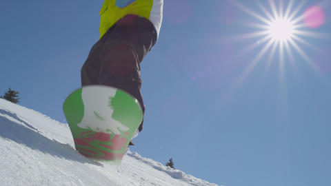 SLOW MOTION: Snowboarder jumps over camera on sunn Footage
