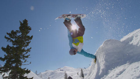 SLOW MOTION: Snowboarding handplant over the sun Footage