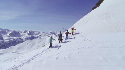 AERIAL: Skiers hiking uphill, carrying the skis Footage