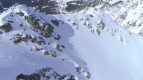 AERIAL: Backcountry skier riding down the big moun Footage
