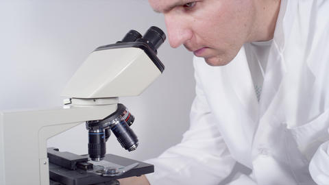 CLOSE UP: Doctor looking into the microscope Footage