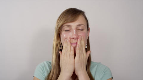 Young woman applying face moisturizer Footage