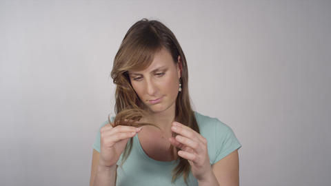 Woman looking at her splitted ends Footage