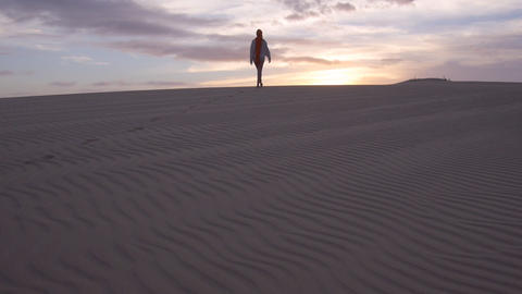 AERIAL: Female walking through a desert at sunrise Footage