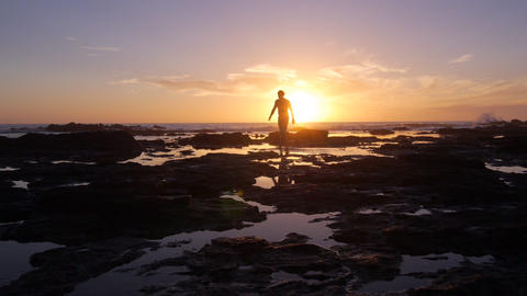 AERIAL: Man Walking Into The Water At Sunset stock footage