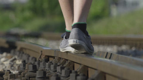 SLOW MOTION CLOSE UP: Walking on railroad track in Footage