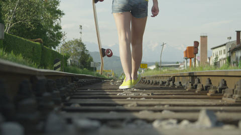 SLOW MOTION: Woman walking on railroad holding a l Footage