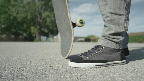 SLOW MOTION CLOSE UP: Skateboarder Picks Up His Sk stock footage
