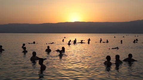 People float in the dead sea during sunrise Footage