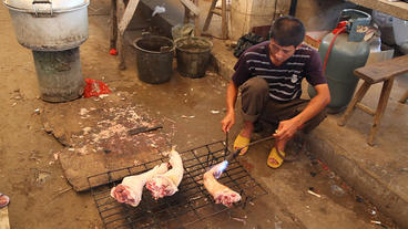 Chinese Cook Cleaning Pig Legs stock footage