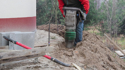 Man compacting soil with use of soil compactor Live Action