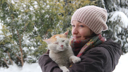 Woman and cat standing outside in snowy winter Footage