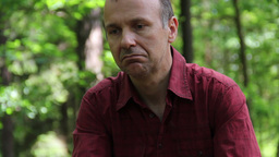 Sad, Pensive Man Sitting In The Forest 6 stock footage