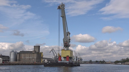 Huge port crane on a barge floats on the river Live Action