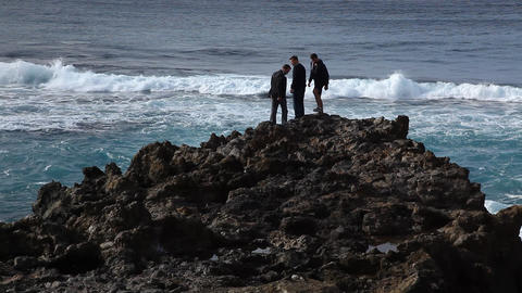 Three guys on black lava beach Footage