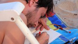 Young Man Laying On Sand,drawing Something stock footage