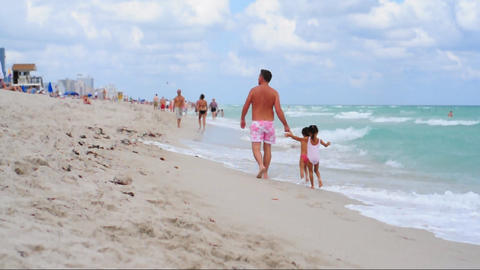 Father walking with his kids on the beach Footage