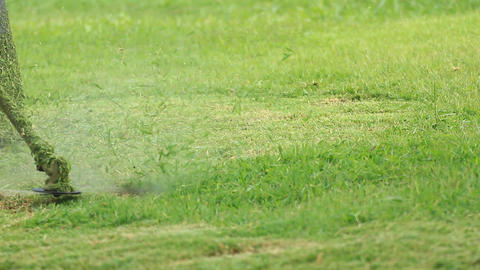 mows overgrown green grass by petrol trimmer Stock Video Footage